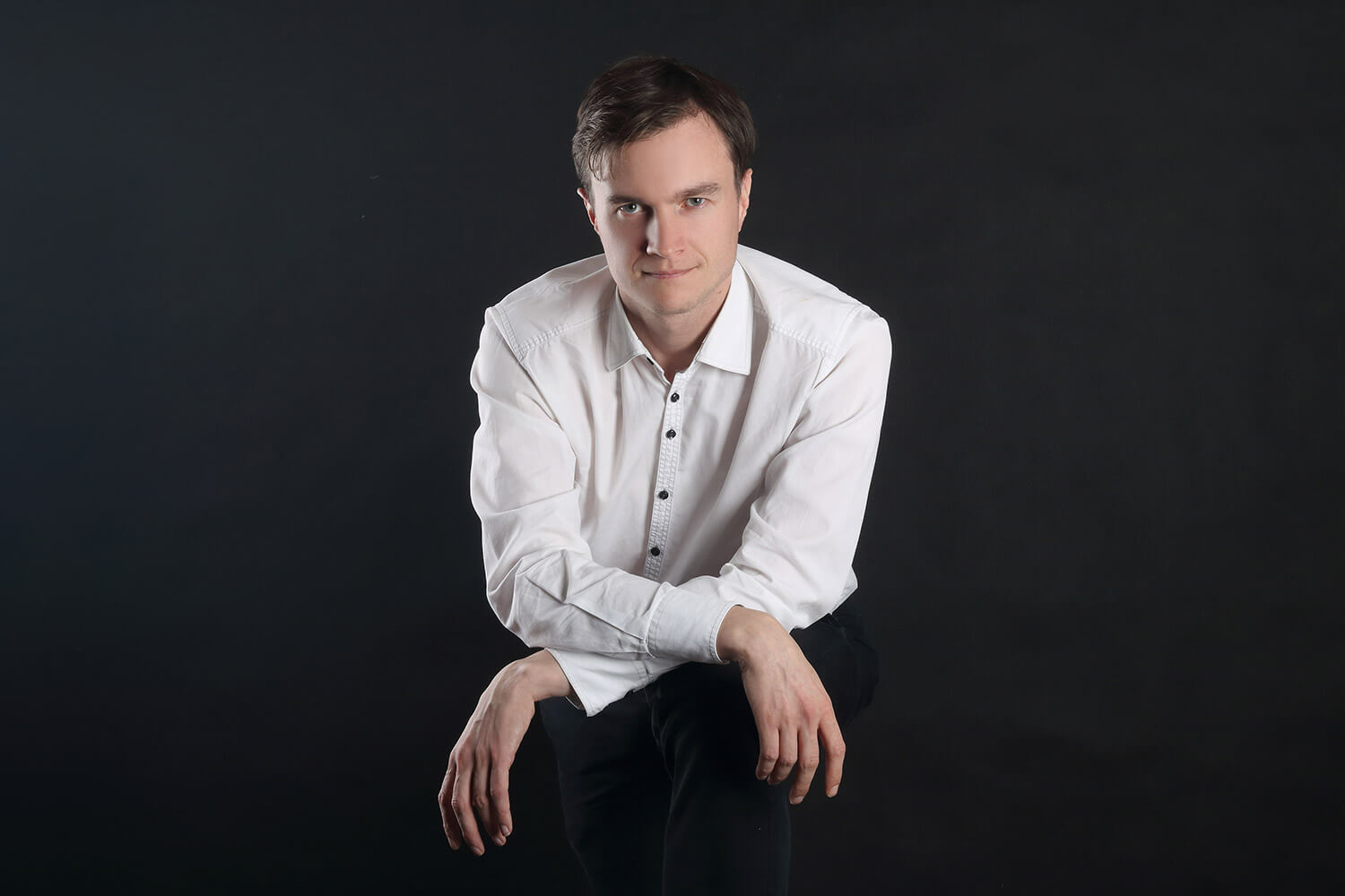 male business portrait in a white shirt on a dark background
