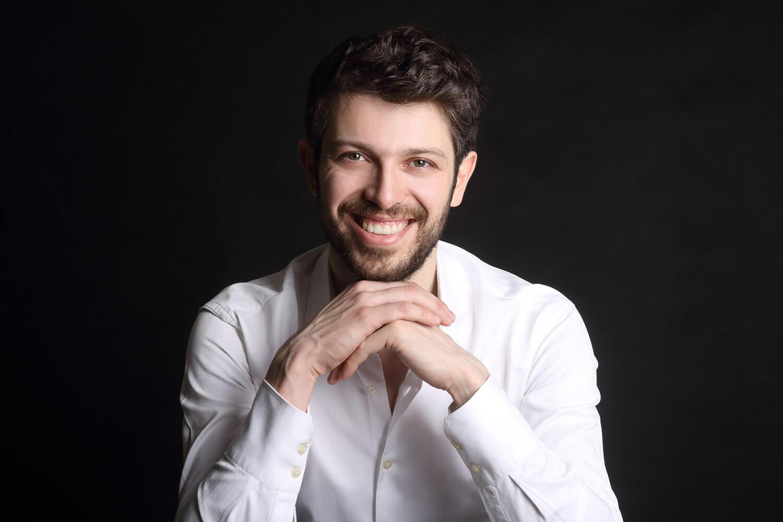 mužský business portrét v bílé košili a rukama pod bradou na tmavém pozadí