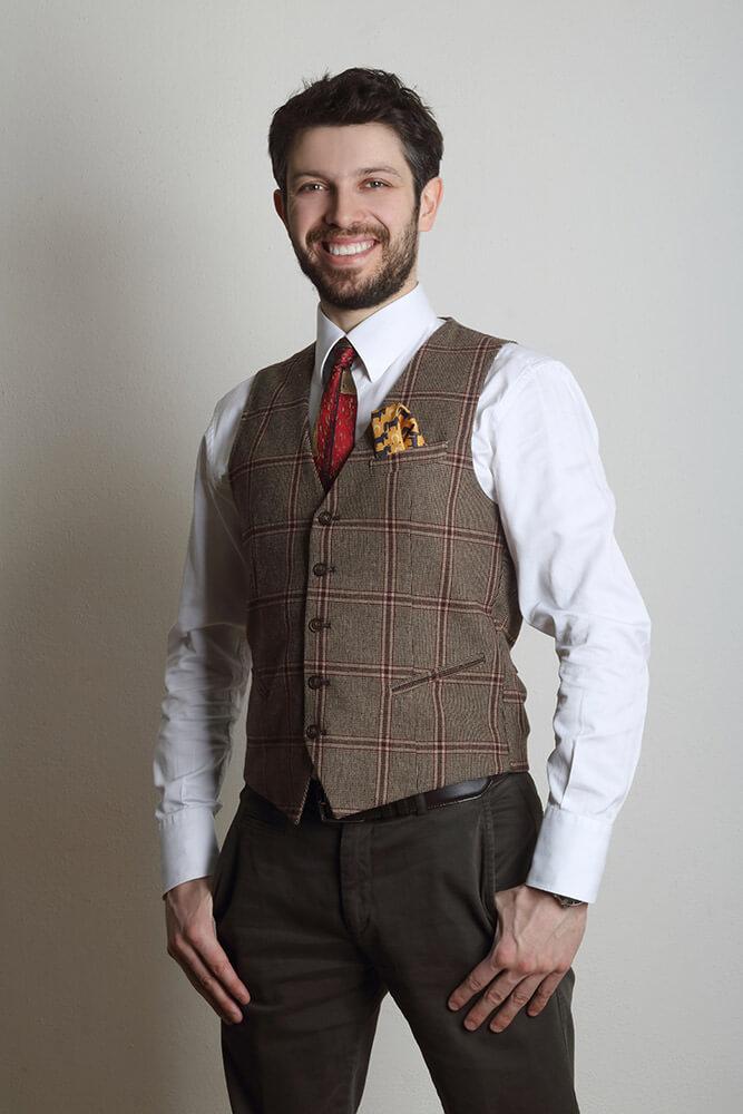 mužský business portrét v bílé košili a tvídové vestě, s rukama v kapsách na světlém pozadí
