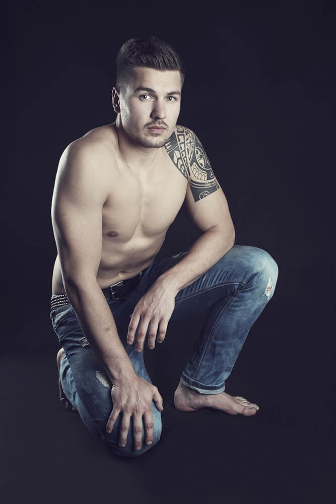 portrait of a man with a tattoo on a black background