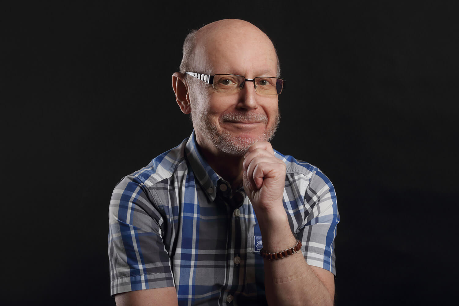 male portrait in a checked shirt and with glasses on a black background