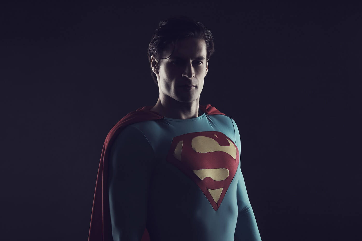 male portrait in a Superman costume on a black background, with light from the side