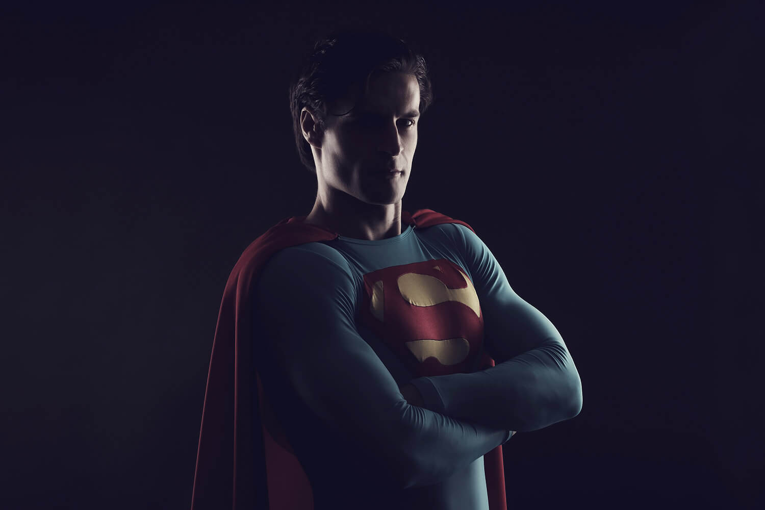 male portrait in a Superman costume and with folded arms on a black background, with light from the side