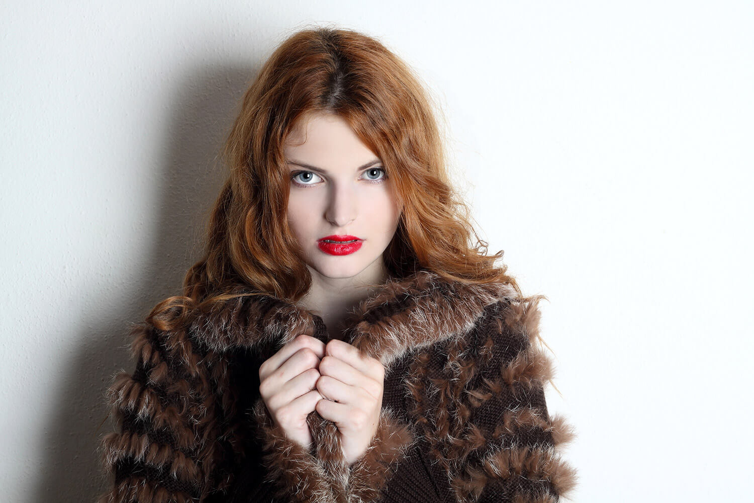 portrait of a woman in a fur jacket on a light background