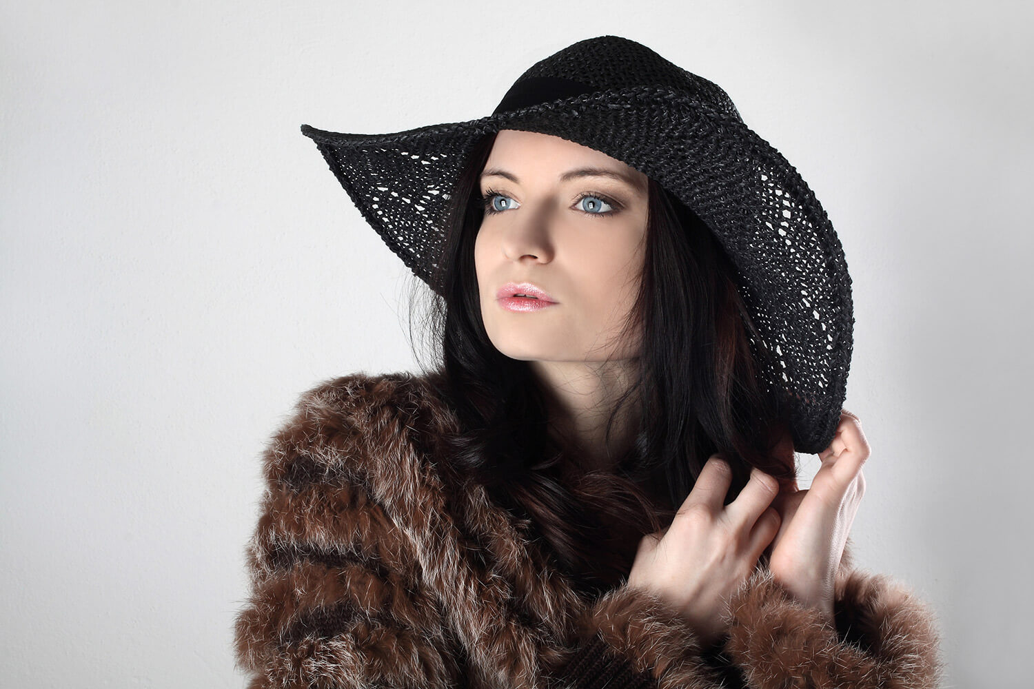 portrait of a woman in a fur jacket and with a hat on a light background