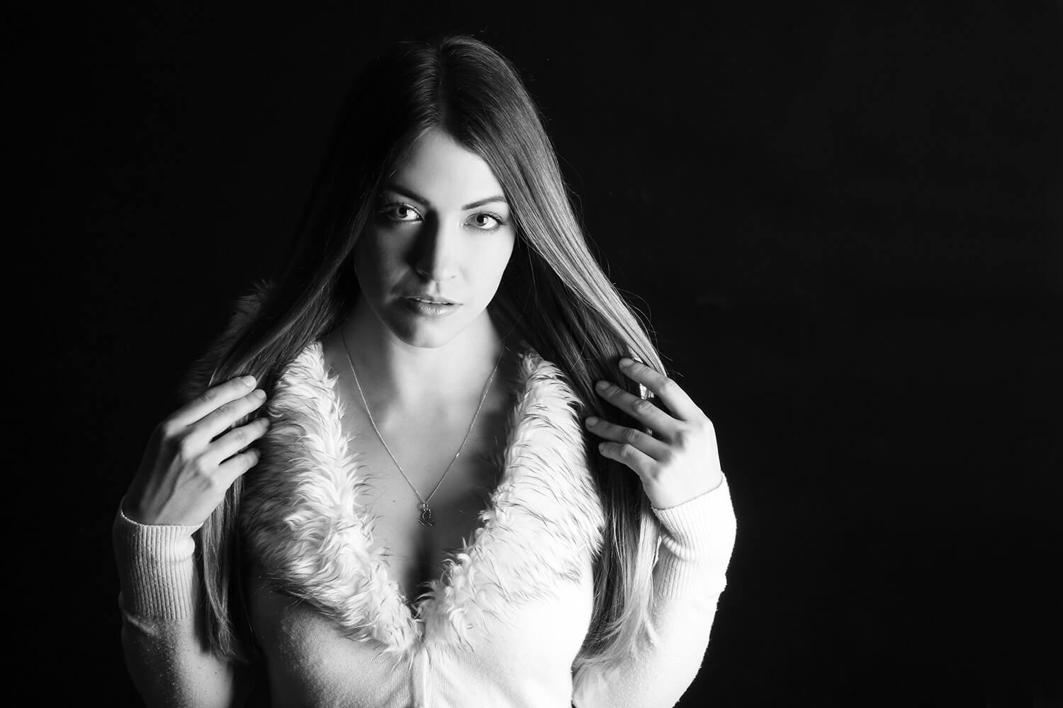 black and white portrait of a woman in a white sweater on a dark background