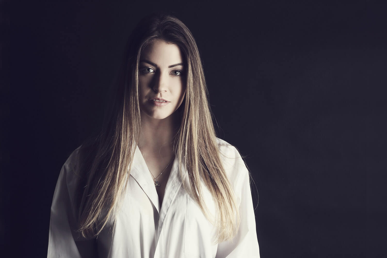ženský portrét v bílé košili na tmavém pozadí