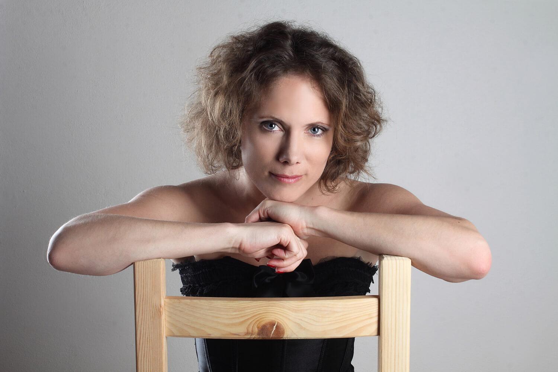 ženský portrét se židlí na světlém pozadí