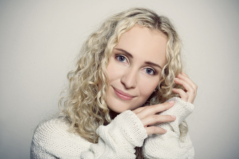 ženský portrét v bílém svetru na kouřovém pozadí