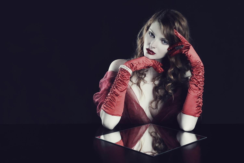boudoir fotografie ženy s červenou látkou a rukavicemi na tmavém pozadí
