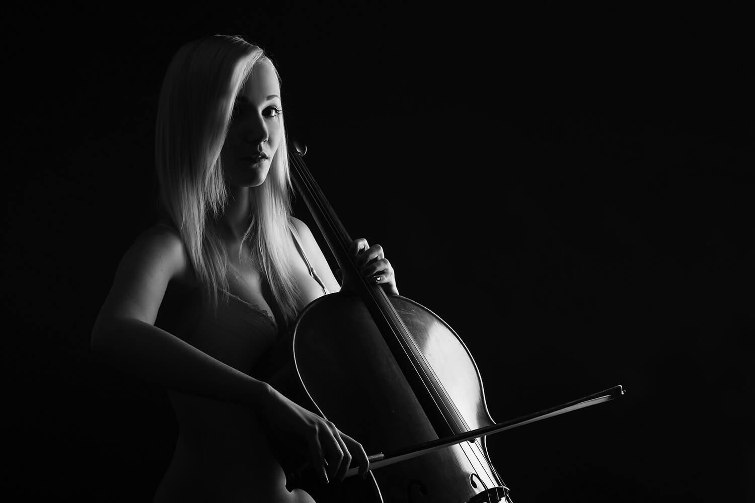 black and white boudoir photo of a woman in lingerie and with a cello on a dark background