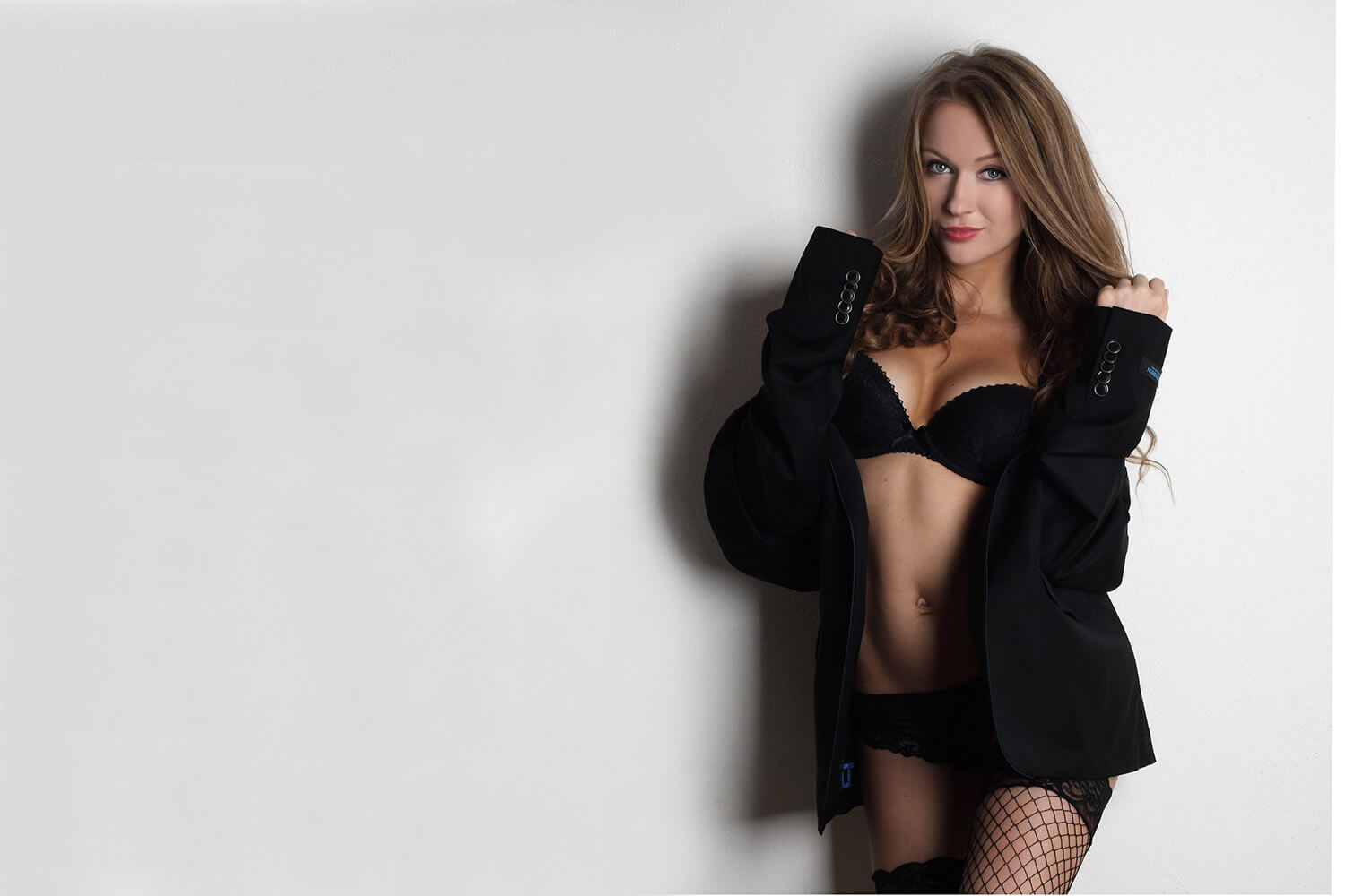 boudoir photo of a woman in lingerie and a black jacket