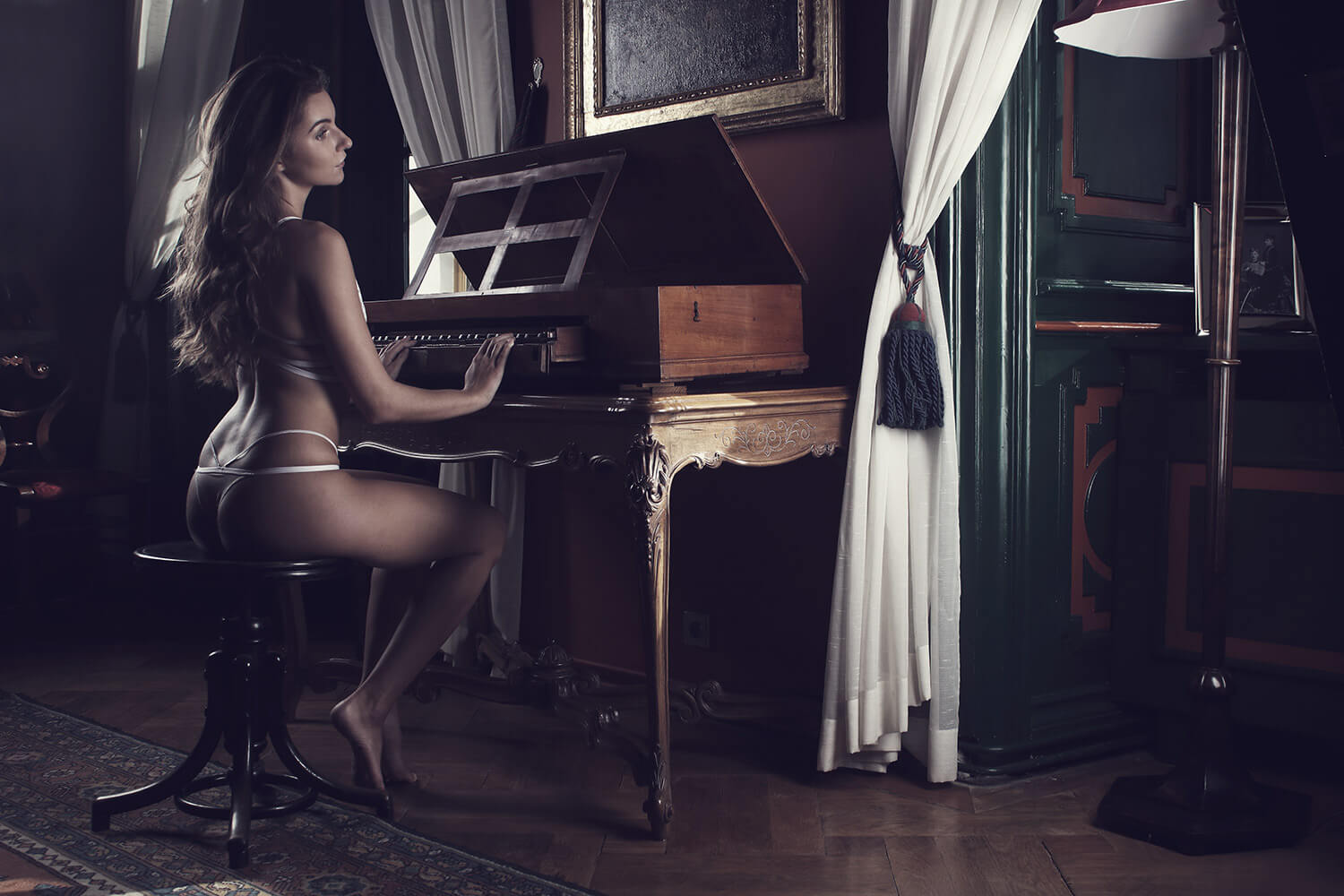 boudoir photo of a woman in lingerie playing the piano in the castle interior