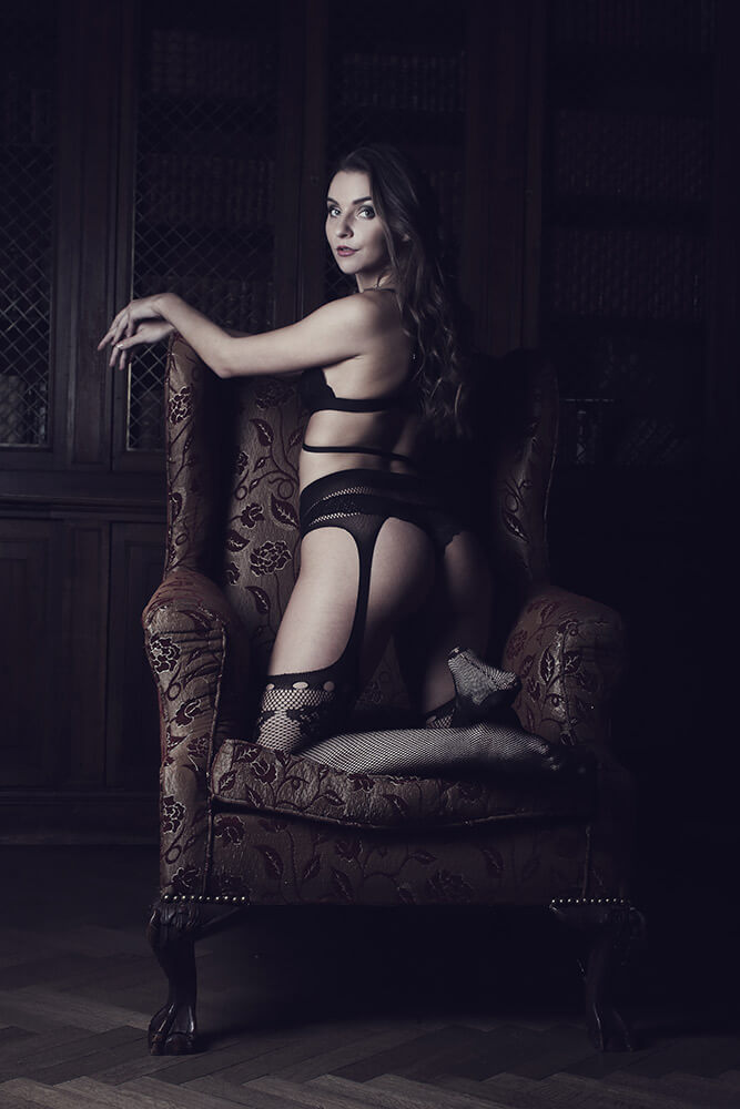 boudoir photo of a woman in lingerie on a historic armchair in the interior of the castle