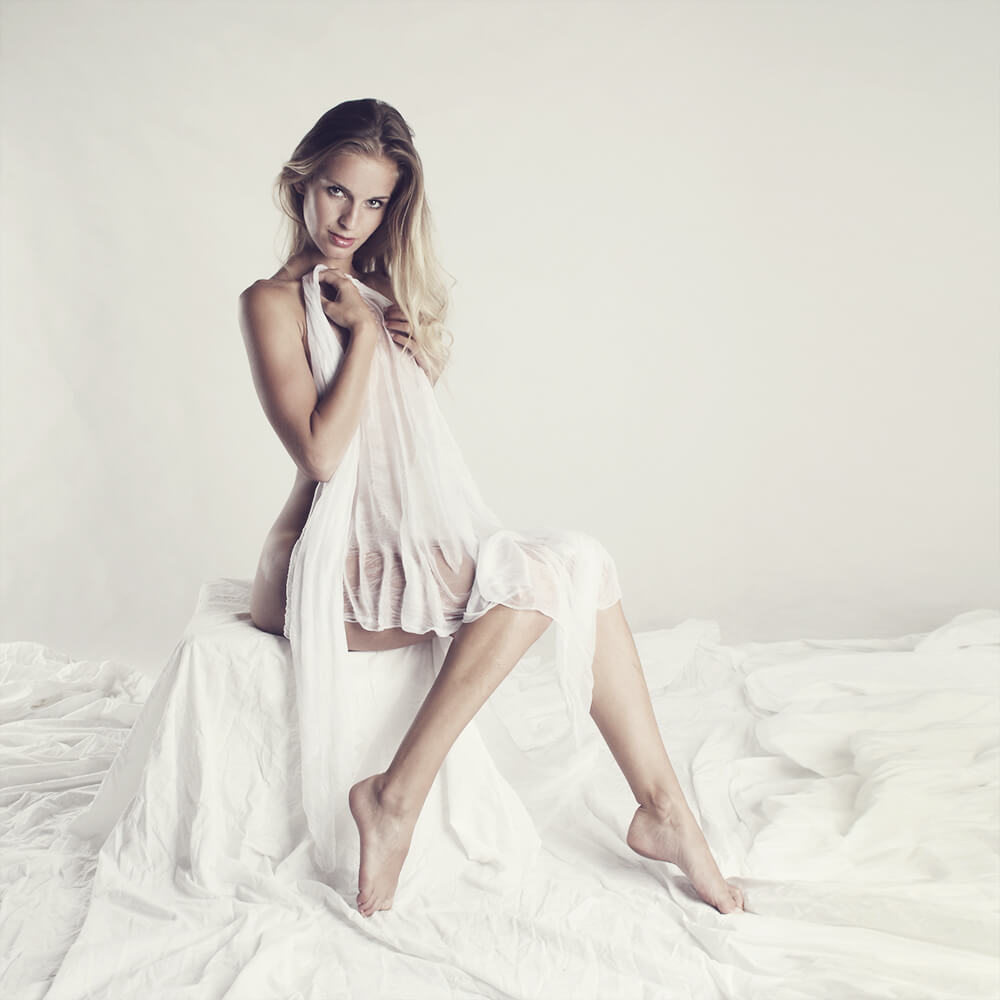 boudoir photo of a woman covered with a white cloth on a light background