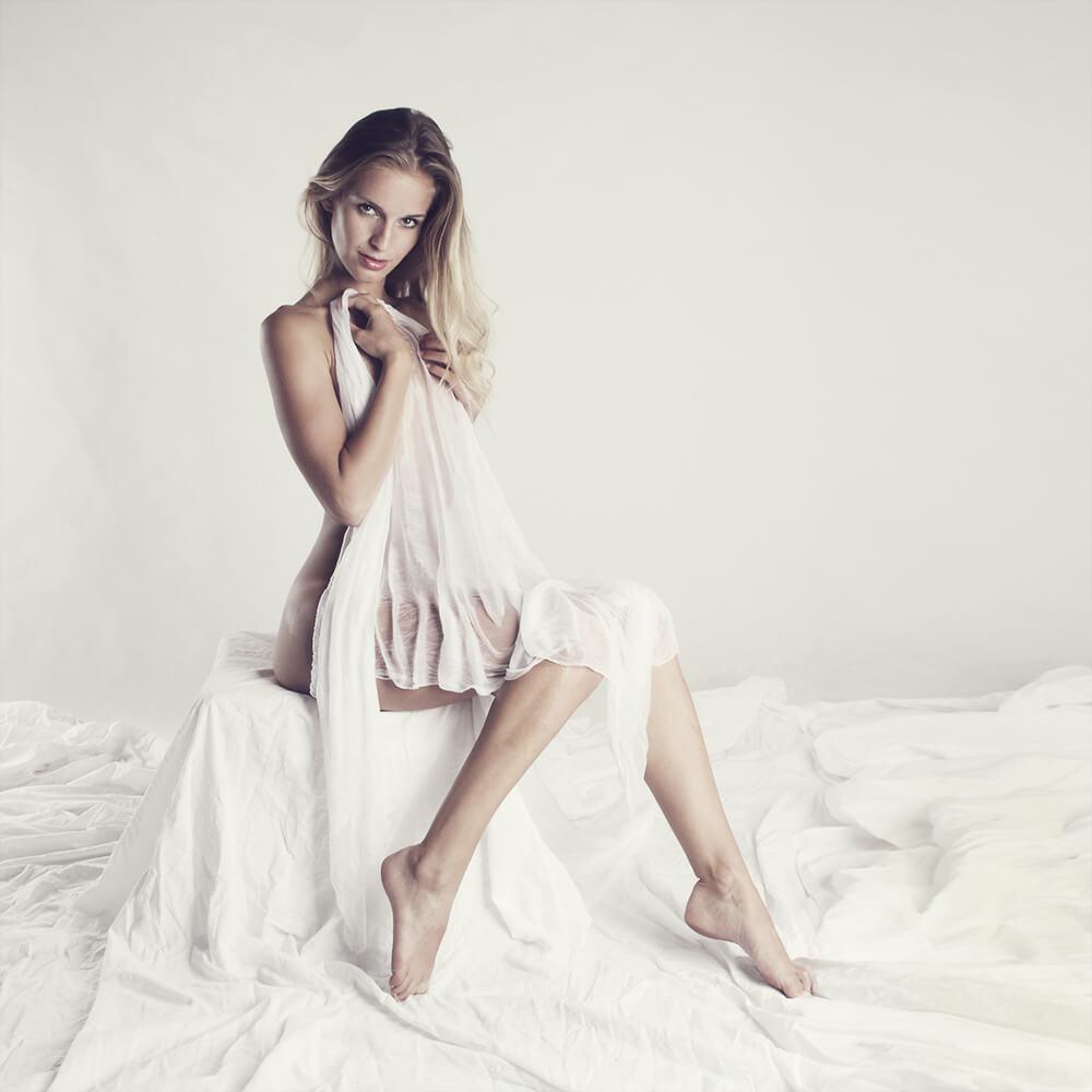 boudoir fotografie ženy zakryté bílou látkou na světlém pozadí
