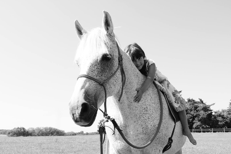 černobílá rodinná fotografie holčičky sedící na koni v přírodě