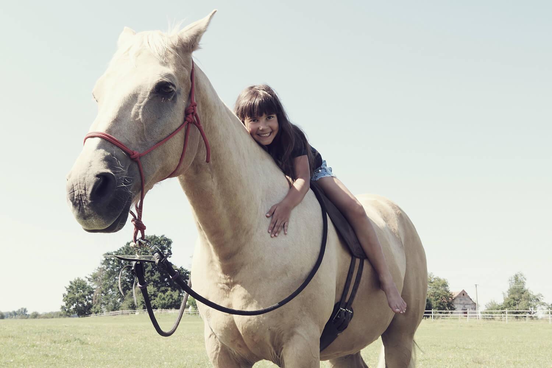 rodinná fotografie holčičky sedící na koni v přírodě