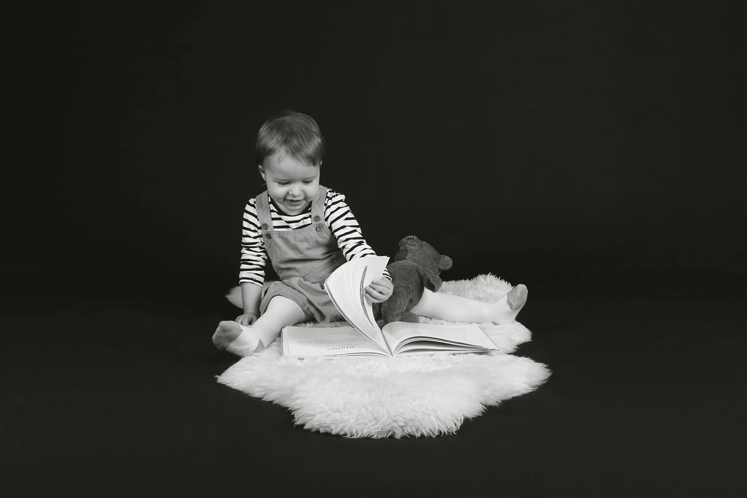 black and white family photo of a little girl with a book on a dark background