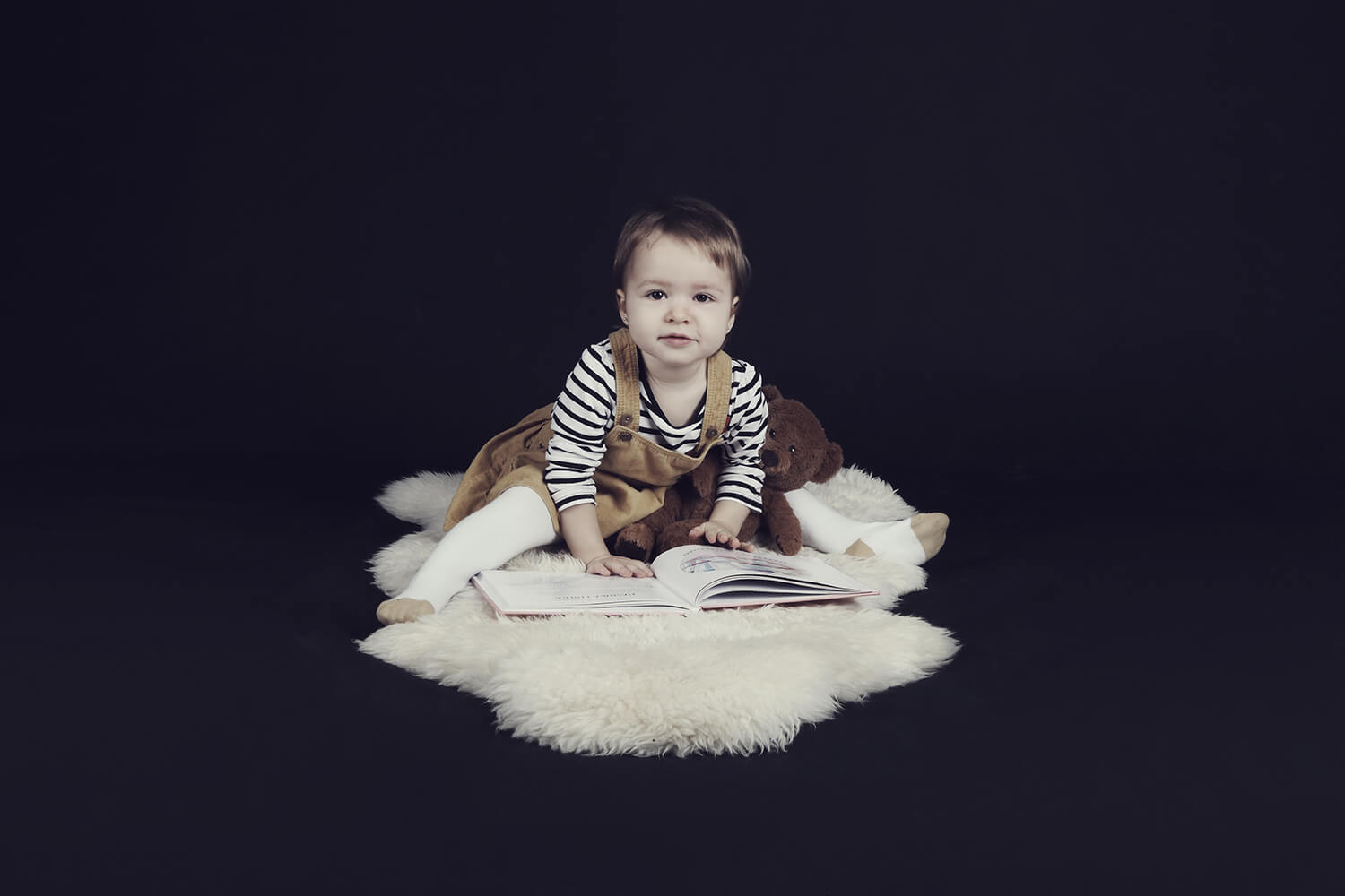 family photo of a little girl with a book on a dark background