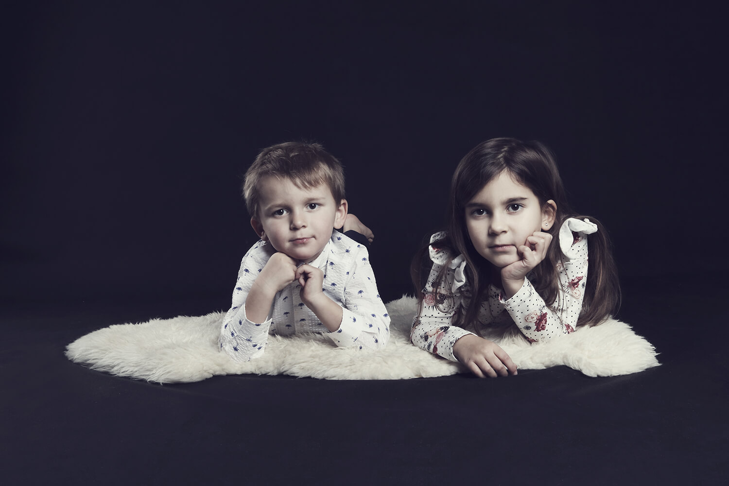 family photo of siblings lying on their bellies on a dark background