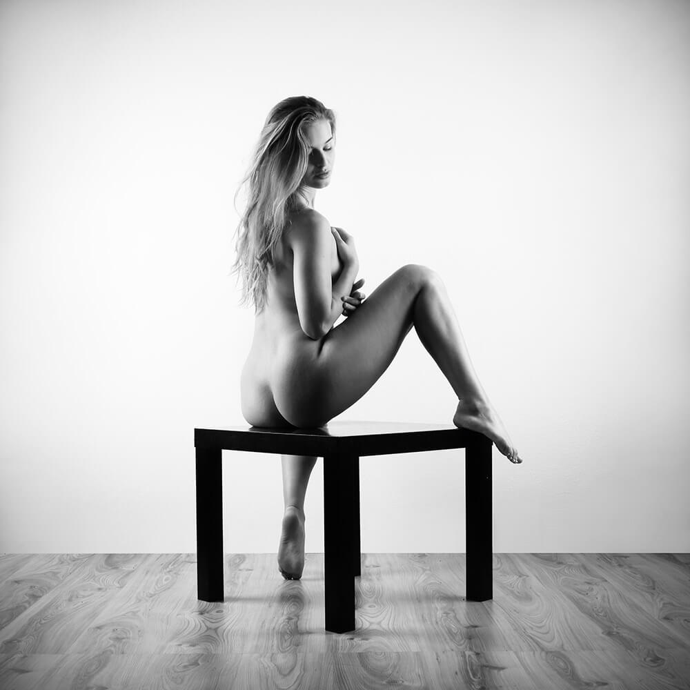 black and white fine art nude of a woman sitting on a coffee table on a light background