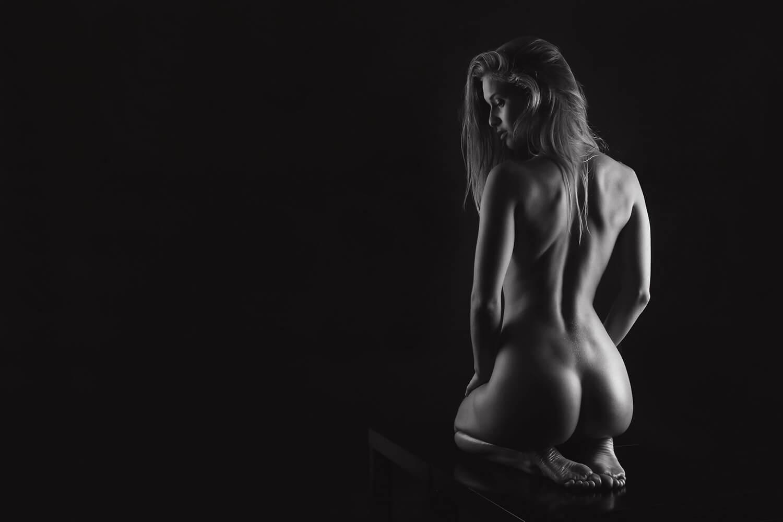černobílý ženský umělecký akt na černém pozadí se světlem z boku