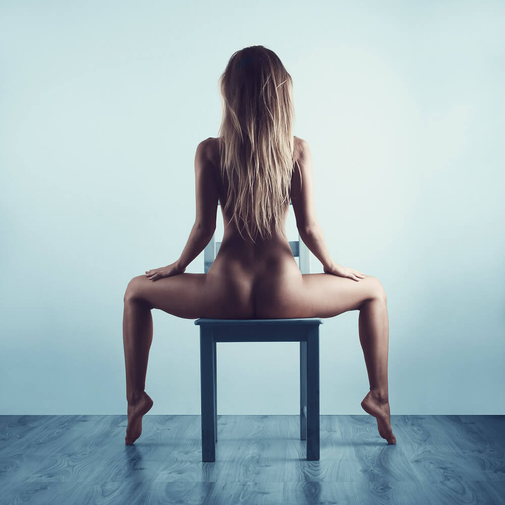 fine art nude of a woman sitting on a chair toned in blue