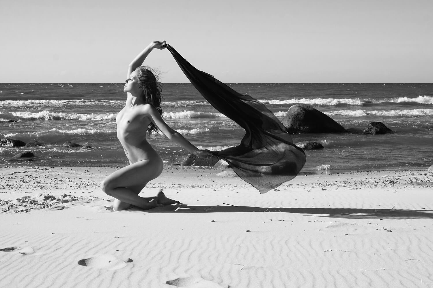 black and white fine art nude of a woman with dark fabric on the beach by the sea