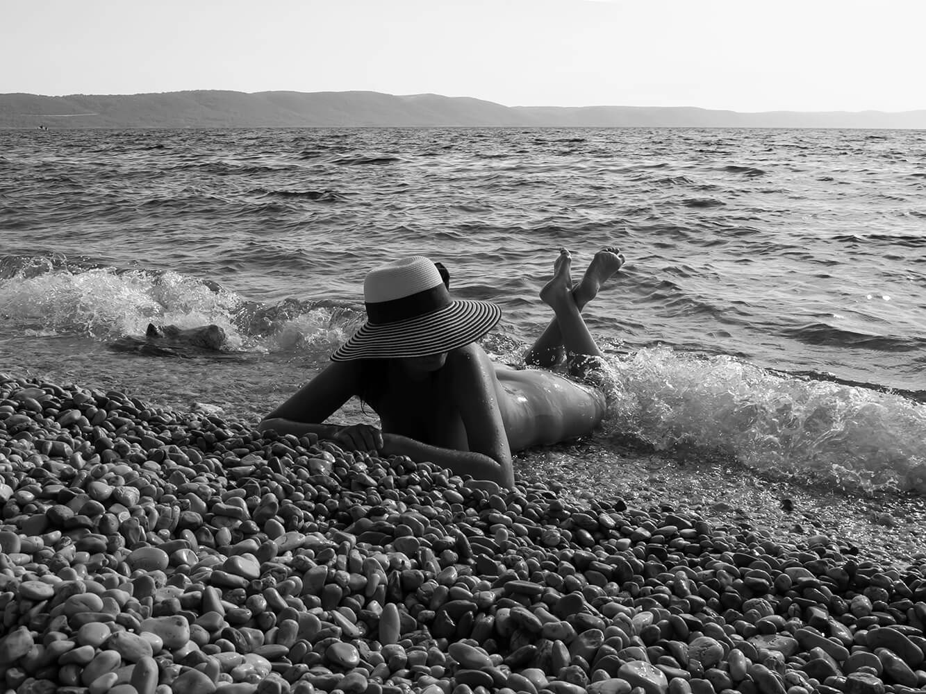 black and white fine art nude of a woman on a pebble beach