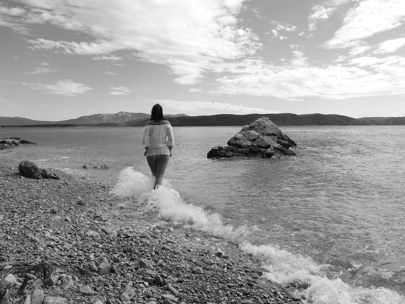black and white fine art nude of a woman standing on pebble beach