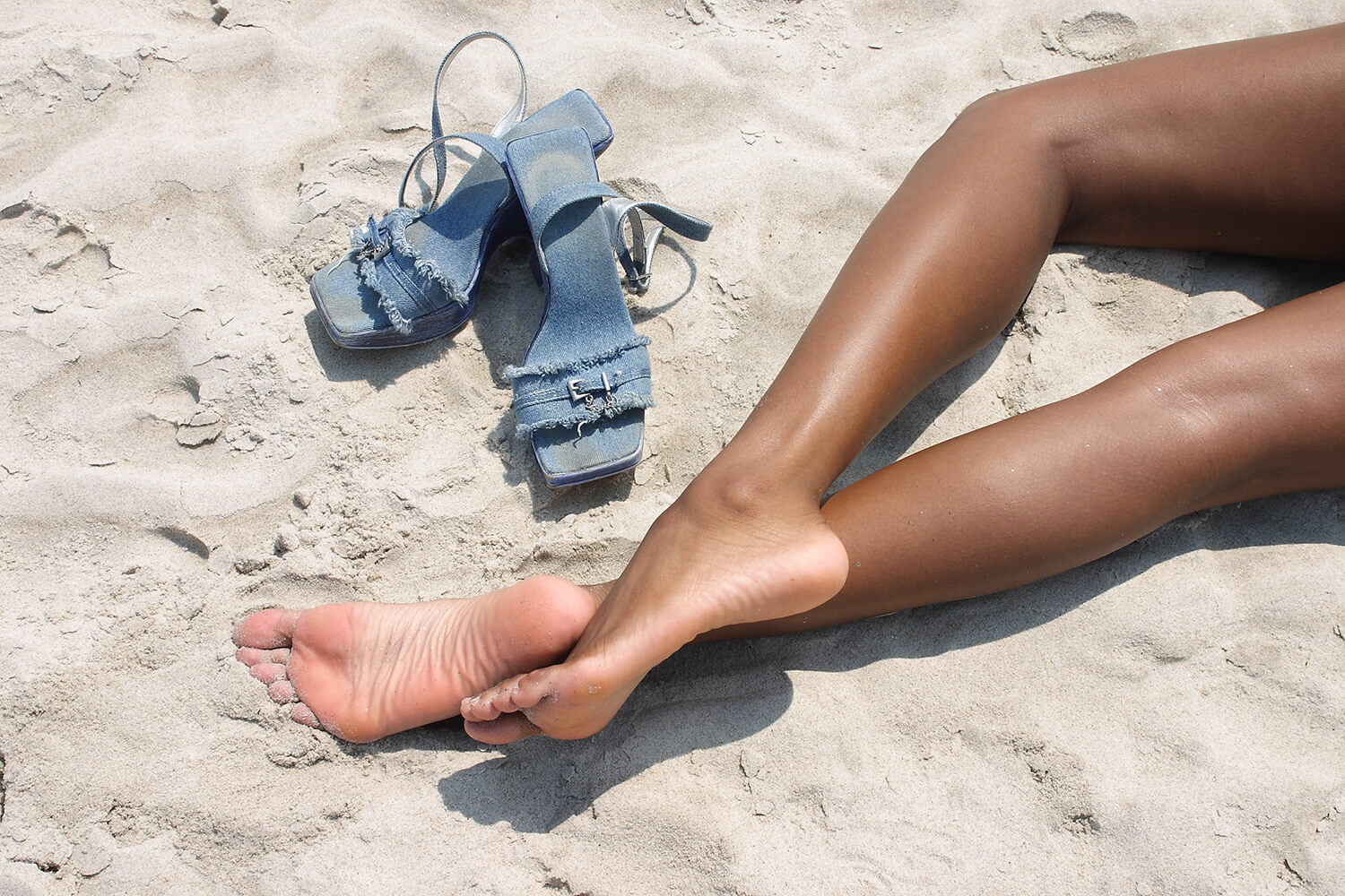 lifestyle photo of female bare feet and blue summer shoes on the sand