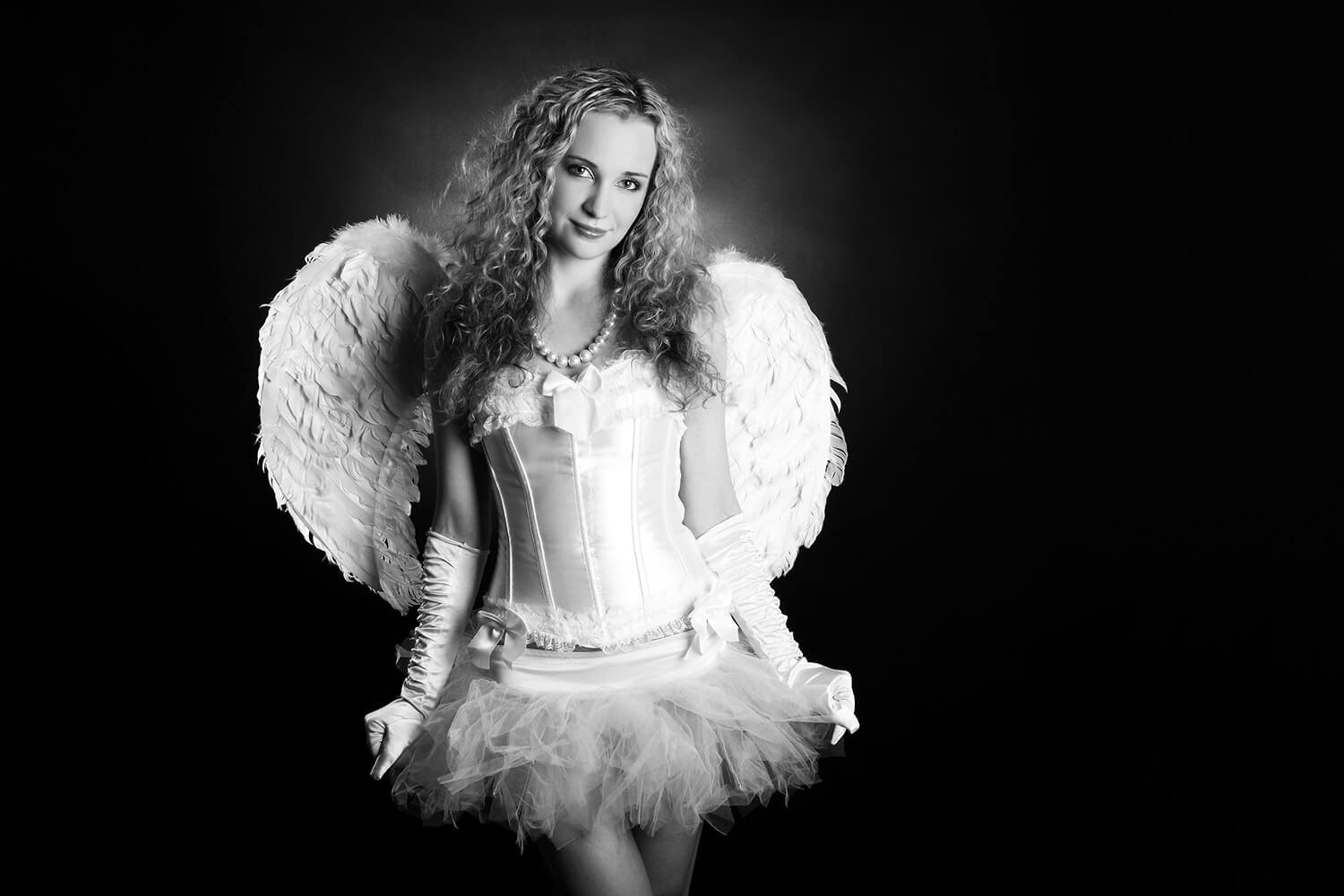 black and white fashion photo of a woman in a white dress and with angel wings