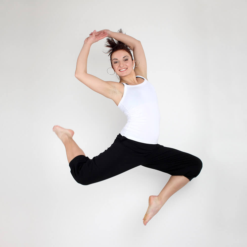 lifestyle photo of a jumping woman in a white tank top and black leggings