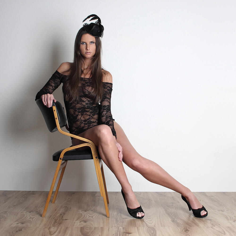 fashion photo of a woman in a black lace top and with a fascinator on her head