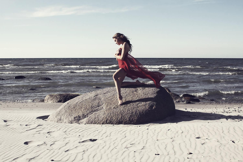 fashion fotografie ženy s červenou látkou na velkém kameni na pláži