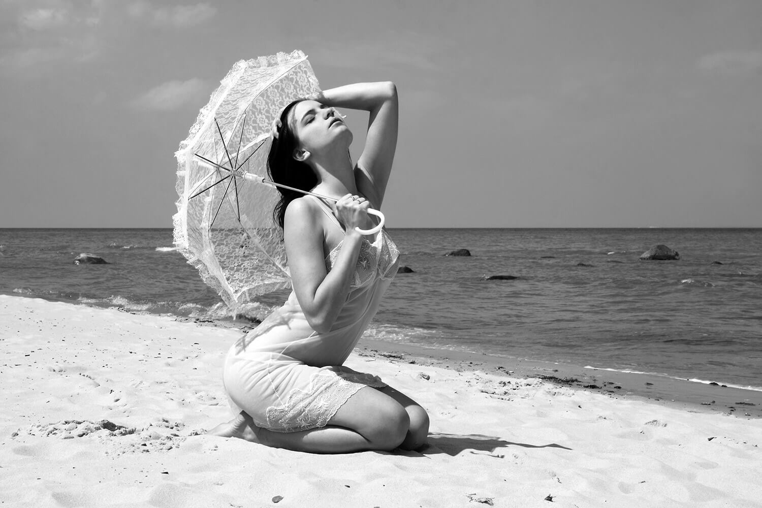 black and white fashion photo of a woman in a negligee and with an umbrella on the beach