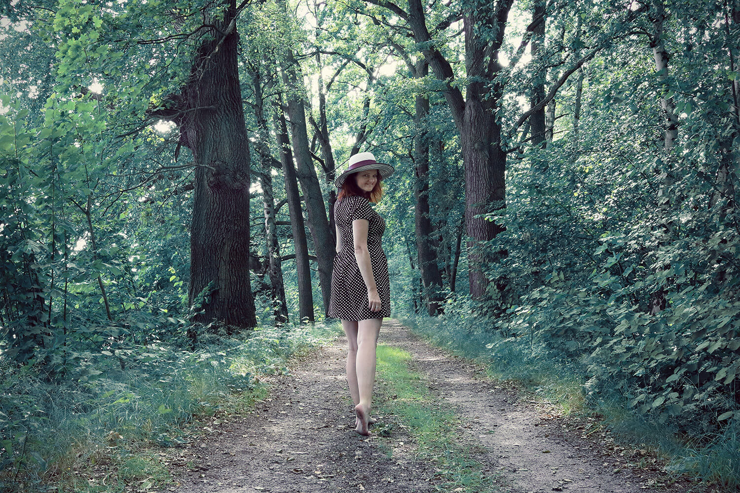 photo of a woman in a dotted dress and a hat in nature
