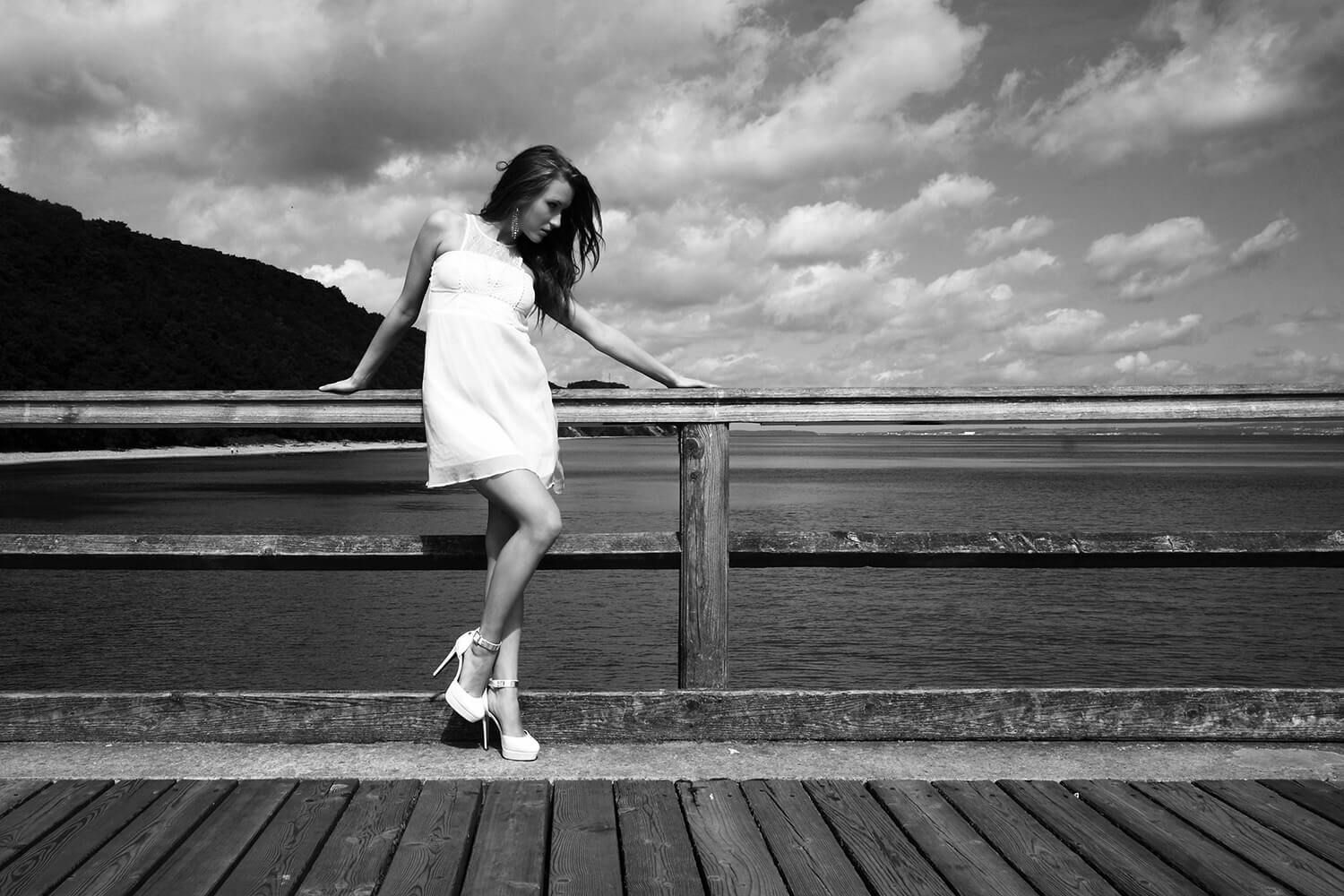 black and white fashion photo of a woman in a white dress on the pier