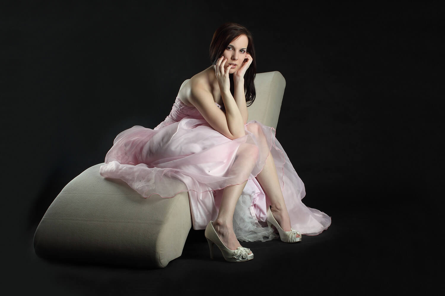 fashion photo of a woman in a pink evening dress sitting on a sofa