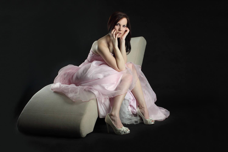 fashion fotografie ženy v růžových večerních šatech sedící na otomanu