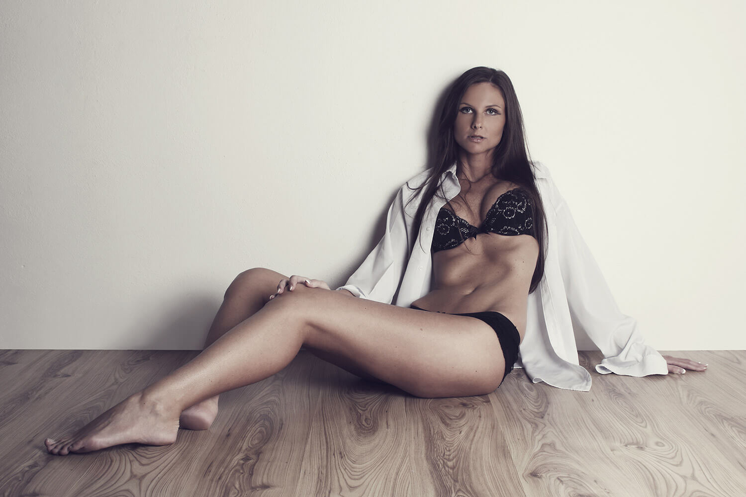 fashion photo of a woman in black lingerie and a white shirt sitting on the floor