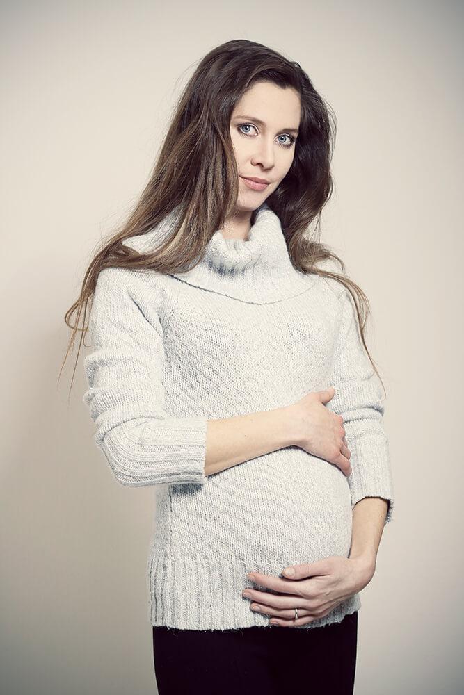 těhotenská fotografie ve světlém svetru na světlém pozadí