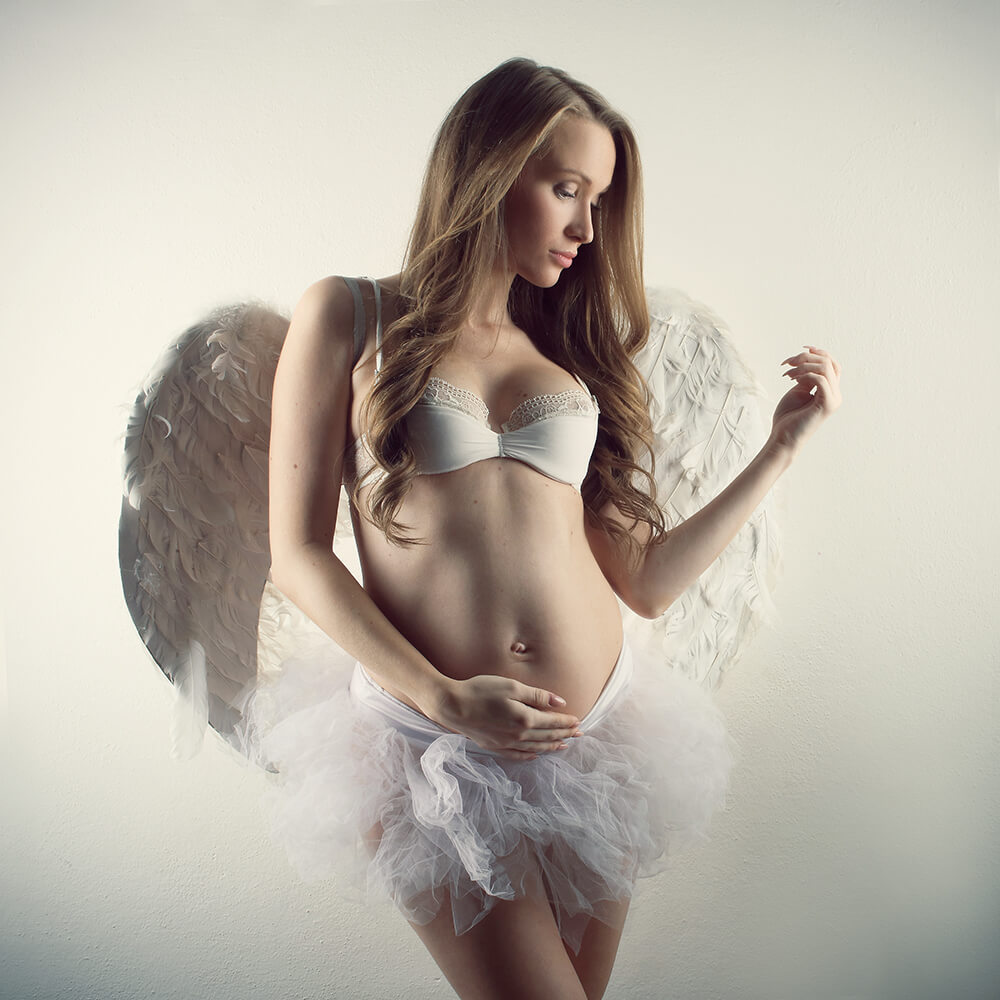 těhotenská fotografie s baletní sukní a křídly na světlém pozadí