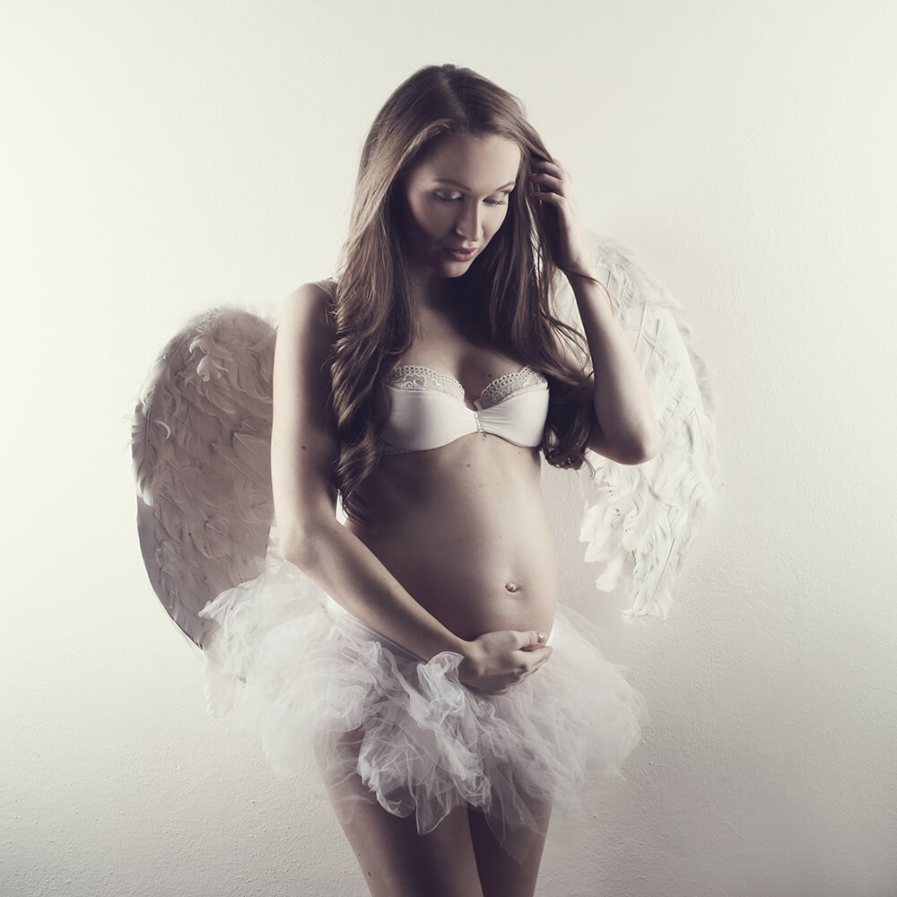 pregnancy photo with a ballet skirt and angel wings on a light background