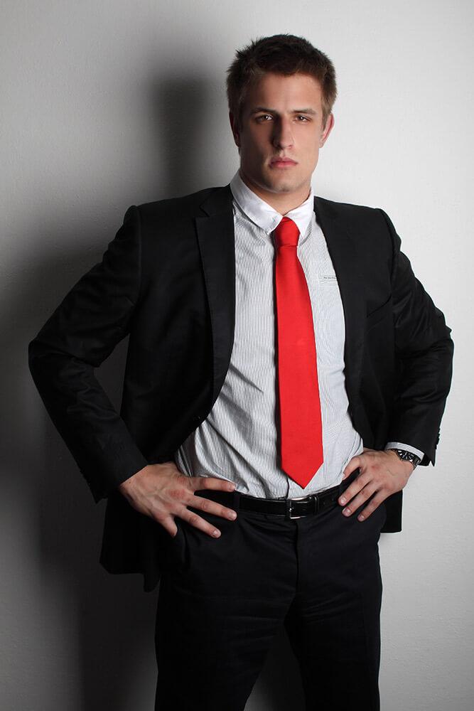 mužský business portrét v černém obleku s červenou kravatou na světlém pozadí
