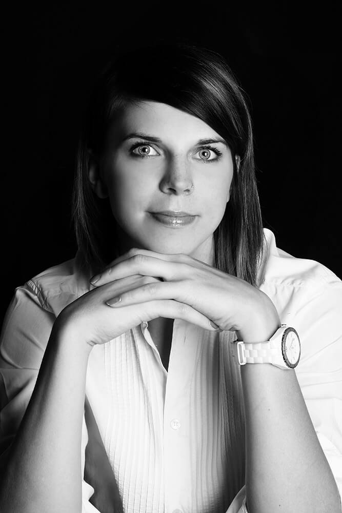 black and white female business portrait in a white shirt on a dark background