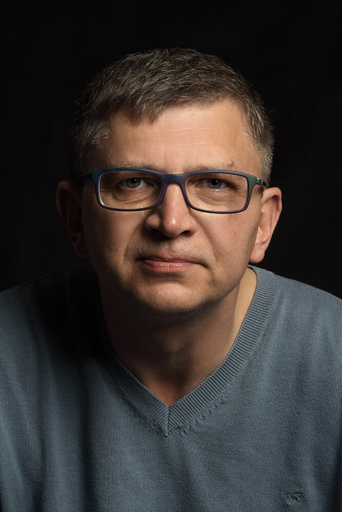 male business portrait in a gray sweater on a dark background