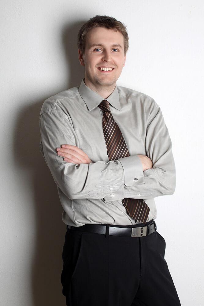 mužský business portrét v šedé košili s kravatou na světlém pozadí