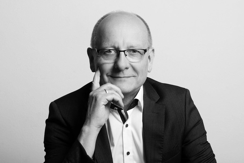 černobílý mužský business portrét v bílé košili a černém saku na světlém pozadí